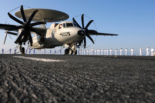 An E-2C Hawkeye sits on the flight deck of USS Abraham Lincoln while sailors man the rails.の写真素材 [FYI02692912]