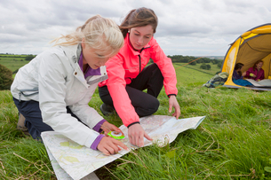 Girls looking down at compass and map in rural fieldの写真素材 [FYI02692931]