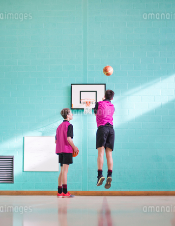 High school students playing basketball in gym classの写真素材 [FYI02692944]