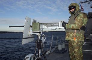 U.S. Navy Petty Officer mans a .50 caliber M2 machine gun.の写真素材 [FYI02692948]