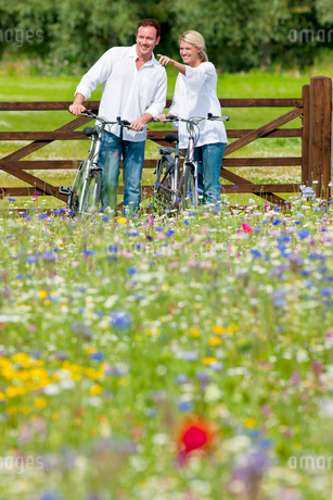 Couple with bicycles pointing in wildflower fieldの写真素材 [FYI02692954]