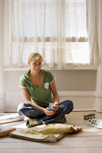 Woman decorating at home, sitting on floor beside window with wallpaper samples and mug, smilingの写真素材 [FYI02692991]