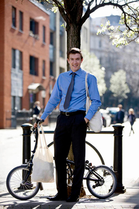 A businessman holding his bicycle, carrying shopping bagsの写真素材 [FYI02692996]