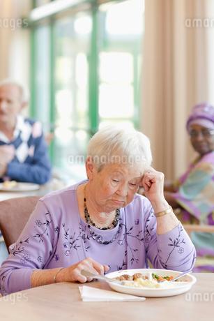 A senior woman having lunch looking sadの写真素材 [FYI02693007]