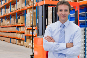 Portrait Of Businessman In Warehouse With Fork Liftの写真素材 [FYI02693009]