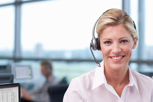 Portrait of smiling businesswoman wearing headset in officeの写真素材 [FYI02693010]