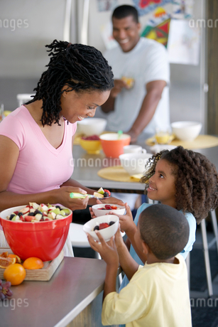 Two generation family preparing food at home, mother serving fruit salad to children (6-9)の写真素材 [FYI02693037]