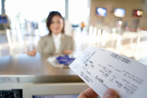 Businesswoman checking in at airport, focus on boarding pass in check-in attendant窶冱 hands in foreの写真素材 [FYI02693044]