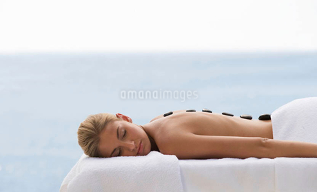 A young woman receiving a hot stone holistic treatmentの写真素材 [FYI02693051]