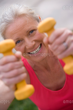 Active senior woman, in pink sports vest, exercising with dumbbells, close-up, front view, portraitの写真素材 [FYI02693063]