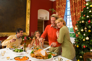 Family having Christmas dinner, woman embracing husband cutting turkeyの写真素材 [FYI02693081]