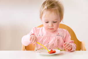 Baby girl in high chair eating strawberriesの写真素材 [FYI02693096]