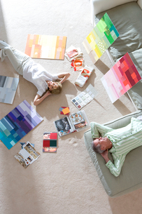 Senior couple lying on floor and sofa at home, looking at colour charts, hands behind head, smiling,の写真素材 [FYI02693117]