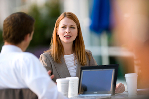 Businesswoman and businessman sitting at pavement cafe table with laptop (differential focus)の写真素材 [FYI02693118]