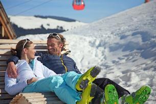 Couple relaxing on wooden chair in ski resortの写真素材 [FYI02693123]