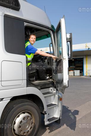 Truck driver sitting in cab of semi-truck and closing doorの写真素材 [FYI02693138]