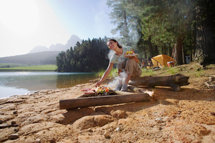 Family having lunch on lakeside camping trip, woman cooking food in foreground, smilingの写真素材 [FYI02693141]