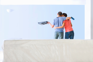 Couple with paint roller and tray kissing and looking at freshly painted living room wallの写真素材 [FYI02693145]
