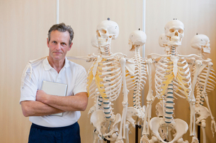 Portrait of confident sports scientist standing next to skeleton modelsの写真素材 [FYI02693153]
