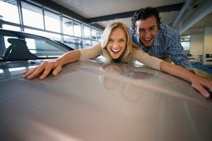 Excited couple embracing bonnet of new silver car in large showroom, smiling, portrait (surface leveの写真素材 [FYI02693154]