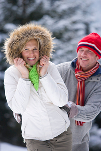 Smiling couple in snowy outdoorsの写真素材 [FYI02693156]