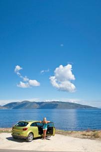 Woman at car looking at sunny ocean viewの写真素材 [FYI02693167]