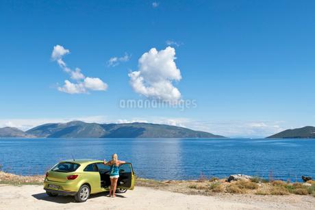 Woman at car looking at sunny ocean viewの写真素材 [FYI02693181]