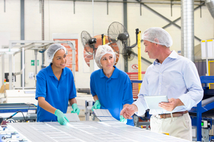 Businessman and technician workers arranging solar cells to form solar panel on production lineの写真素材 [FYI02693183]