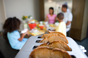 Bread in toaster, family at breakfast table in backgroundの写真素材 [FYI02693209]