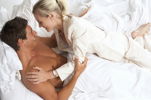 Couple playfighting in bed, woman lying on top of man, smiling, side view, elevated viewの写真素材 [FYI02693210]