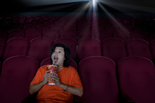 Man with drink in empty cinema making faceの写真素材 [FYI02693231]