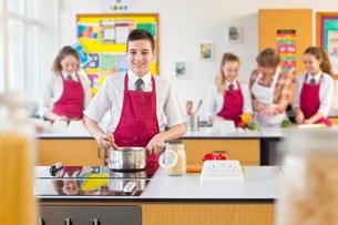 Portrait confident male high school student cooking in home economics classの写真素材 [FYI02693258]