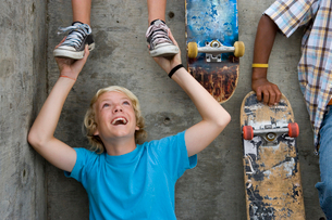 Boy (11-13) holding feet of friend on wall above, by skateboardsの写真素材 [FYI02693259]