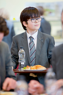Middle school student eating lunch looking away in school cafeteriaの写真素材 [FYI02693276]