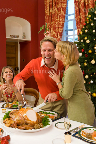 Family having Christmas dinner, woman kissing husband cutting turkeyの写真素材 [FYI02693304]
