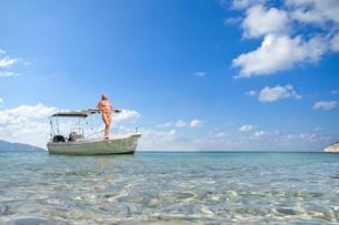Woman standing on boat in sunny oceanの写真素材 [FYI02693333]