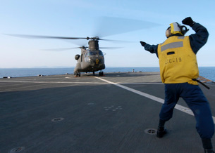 Boatswain's Mate signals to an Army CH-47 Chinook helicopterの写真素材 [FYI02693345]
