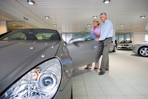 Senior couple looking at new silver convertible car in large showroom, man opening car door, smilingの写真素材 [FYI02693352]