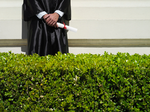 University student in graduation gown holding diploma, mid-section, hedge in foregroundの写真素材 [FYI02693357]