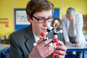 High school student examining molecule model in science classの写真素材 [FYI02693359]