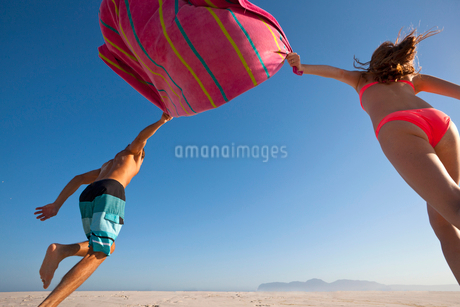 Low Angle View Of Couple On Holiday Running Along Beachの写真素材 [FYI02693367]