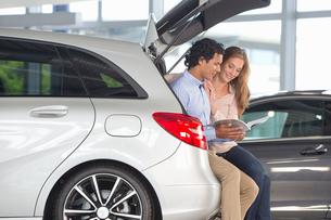 Couple looking at brochure in hatchback of car in car dealership showroomの写真素材 [FYI02693368]