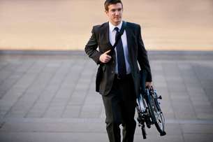 A businessman carrying his folded bicycle to workの写真素材 [FYI02693370]