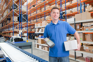 Portrait of smiling worker holding scanner and box at production line in distribution warehouseの写真素材 [FYI02693375]
