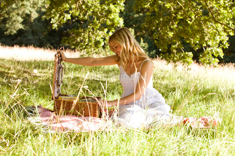A young woman opening a picnic basketの写真素材 [FYI02693385]