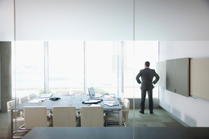Businessman standing with hands on hips at window in conference roomの写真素材 [FYI02693389]