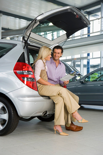 Couple looking at new silver hatchback in car showroom, sitting in open boot, man holding brochure,の写真素材 [FYI02693403]