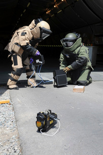 Soldiers dressed in bomb suits examine a suspicious package.の写真素材 [FYI02693413]