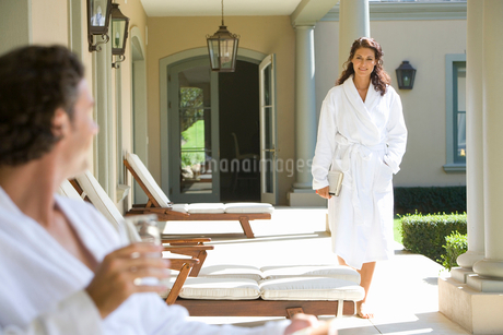 Woman wearing white robe walking towards man sitting with glass of waterの写真素材 [FYI02693418]