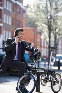 A businessman sitting on a bench, talking on his mobile phoneの写真素材 [FYI02693421]